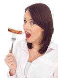 Young Woman Holding a Pork Sausage on a Fork Royalty Free Stock Photos