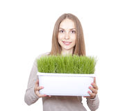 Young Woman Holding Pot of Green Grass Royalty Free Stock Images
