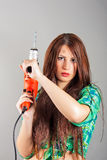 Young woman holding a power tool. Portrait of young woman holding a power tool royalty free stock photo
