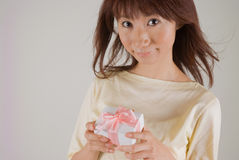 Young woman holding present. Young woman smiling with present in hands Royalty Free Stock Photos