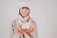 Young woman holding present. Young woman with knit hat holding present Royalty Free Stock Photography