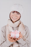 Young woman holding present. Young woman with knit hat holding present Stock Photo