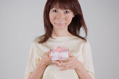 Young woman holding present. Young Asian woman holding present Royalty Free Stock Images