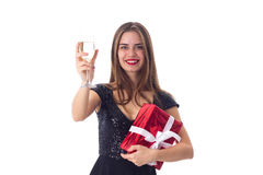 Young woman holding a present and a glass of champagne Royalty Free Stock Images