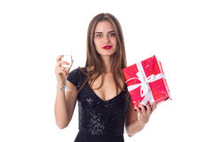 Young woman holding a present and a glass of champagne Royalty Free Stock Photo