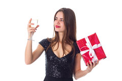Young woman holding a present and a glass of champagne Royalty Free Stock Photography