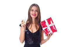 Young woman holding a present and a glass of champagne Stock Photography