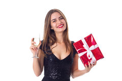 Young woman holding a present and a glass of champagne Stock Photos