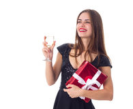 Young woman holding a present and a glass of champagne Stock Photo