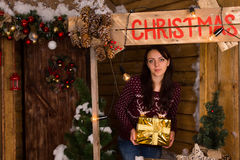 Young Woman Holding Presents at Christmas Booth Stock Photos