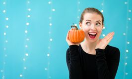 Young woman holding a pumpkin. On a shiny light background Royalty Free Stock Photo