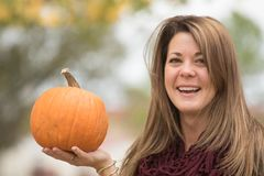 Young woman holding a pumpkin in a fall setting. stock images