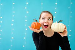 Young woman holding pumpkins. On a shiny light background Stock Photos