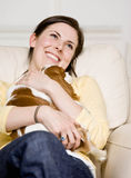 Young woman holding puppy on couch Stock Images