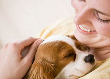Young woman holding puppy on couch Royalty Free Stock Photo