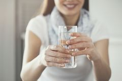 Young woman holding  pure glass of water. Young woman holding   pure glass of water Royalty Free Stock Photos