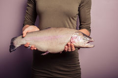 Young woman holding a rainbow trout Royalty Free Stock Images