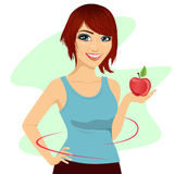 Young woman holding a red apple showing thin waist Royalty Free Stock Images