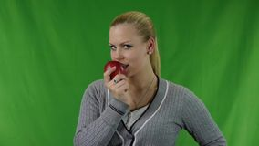 Young woman holding red apple and smiling. stock video