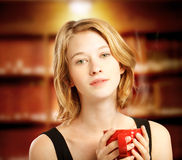 Young woman holding red coffee mug Royalty Free Stock Photos