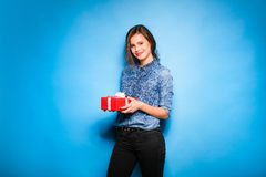 Young woman holding red gift in hands Stock Images