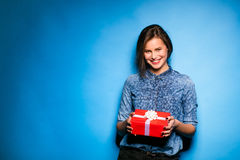 Young woman holding red gift in hands Royalty Free Stock Photography