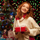 Young woman holding red gift over christmas tree and lights on b Royalty Free Stock Photos