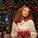Young woman holding red gift over christmas tree and lights on b Royalty Free Stock Photo