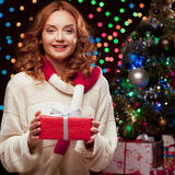 Young woman holding red gift over christmas tree and lights on b Royalty Free Stock Images