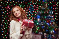 Young woman holding red gift over christmas tree and lights on b Stock Image