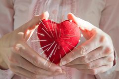 Young woman holding red heart with needles, selective focus. Red heart with needles in it on white background and inscription, Concept of broken heart Royalty Free Stock Photography