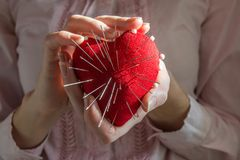 Young woman holding red heart with needles, selective focus. Red heart with needles in it on white background and inscription, Concept of broken heart Stock Photos