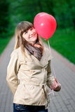 Young woman holding red heart shaped balloon Stock Photo