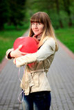 Young woman holding red heart shaped balloon Stock Photography