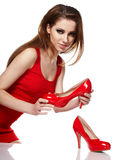 Young woman holding a red shoe. Portrait of a happy young woman holding a red shoe Stock Image