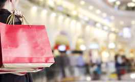 Young woman holding red shopping bag at department store Royalty Free Stock Photography