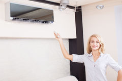 Young woman holding a remote control air conditioner Royalty Free Stock Image