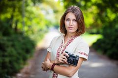 Young woman holding retro style camera in park Stock Photo