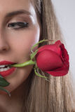 A young woman holding a rose in her mouth Stock Image