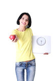 Young woman holding scales and apple Stock Images