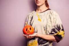 Young woman holding a scary jack-o-lantern Stock Photos