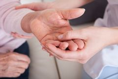 Young woman holding senior woman's hand. Indoor Royalty Free Stock Images