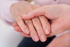 Young woman holding senior woman's hand Stock Photos