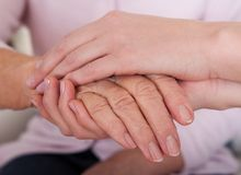 Young woman holding senior woman's hand. Indoor Stock Images