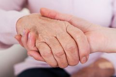 Young woman holding senior woman's hand. Indoor Stock Image