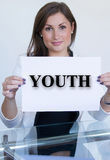 Young woman holding a sheet of paper with the text youth Royalty Free Stock Photo