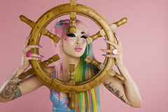Young woman holding ship's wheel in front of her face Stock Photo