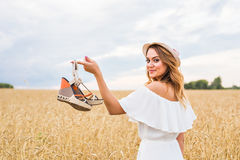 Young woman holding a shoe - sale, consumerism and people concept Royalty Free Stock Photography