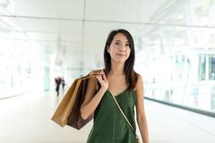 Young Woman holding shopping bag ans walking along the street Royalty Free Stock Image