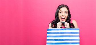 Young woman holding a shopping bag. On a pink background Stock Photos